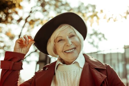 Happy smiling elderly woman touching her hat with two fingers while taking a walk in a park.