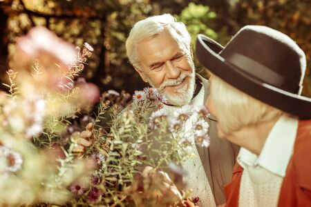 Smiling senior man with grey beard looking at his wife and touching flowers in a garden.