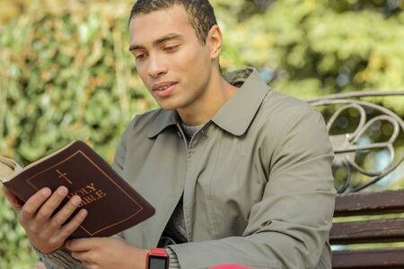 Attentive short-haired guy in grey coat reading bible while visiting park area