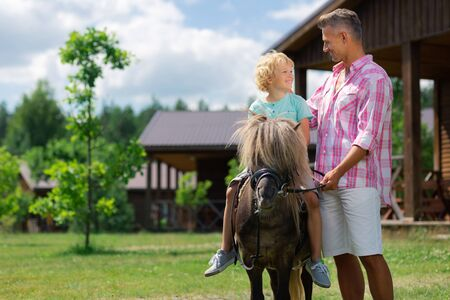 Curly blonde-haired cute son feeling thankful to father while riding horse