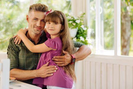 Cute dark-haired daughter hugging her loving handsome daddy wearing hand watch