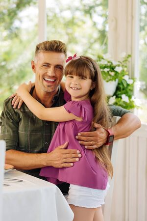Daddy wearing smart watch smiling broadly and hugging his cute daughter