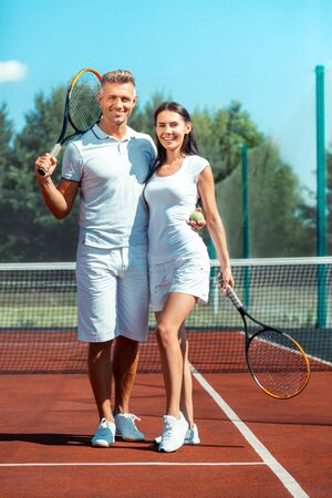 Happy couple feeling satisfied and memorable having sport day on tennis court