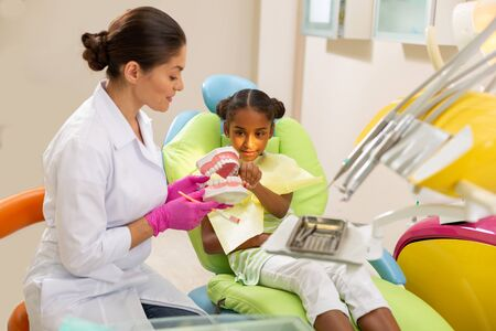 Teeth model with a toothbrush. Female dentist using an artificial teeth model while showing toothbrushing technique to a young female patient sitting next to her