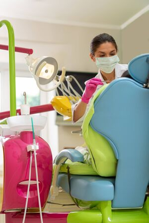 Dentists tools. Concentrated serious dark-haired female dentist applying dental instruments while learning over her patient in a dentists chair