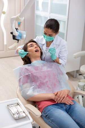 Dental health. Attentive female dentist holding dental tools over a young male patient sitting in a dental chair
