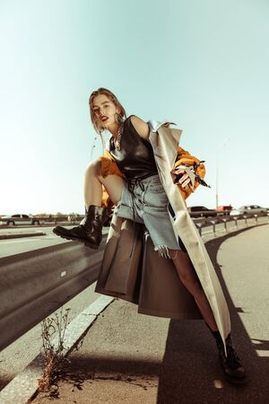 Extraordinary photoshoot . Serious rough woman in a heavy black boots leaning on a metal road fence
