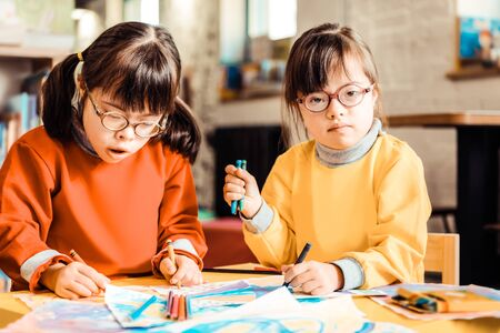 Spending time together. Focused sisters with down syndrome wearing orange and yellow sweaters while visiting developing lessons