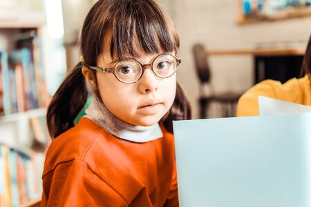 Cute little girl with long bangs and eyeglasses holding open book during individual courses