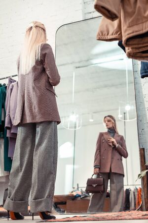 Looking into mirror. Blonde-haired slim woman wearing baggy grey trousers looking into mirror