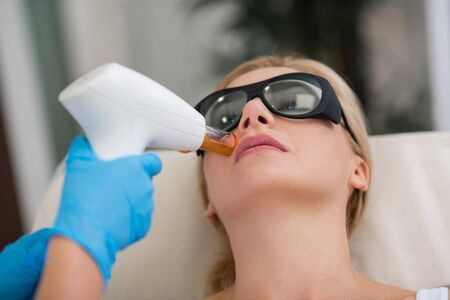 Staying young. Serious blond woman wearing protection glasses getting her face skin treatment in a beauty salon.