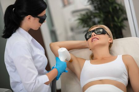 Feeling beautiful. Smiling woman getting laser treatment for her armpits lying near the cosmetologist.