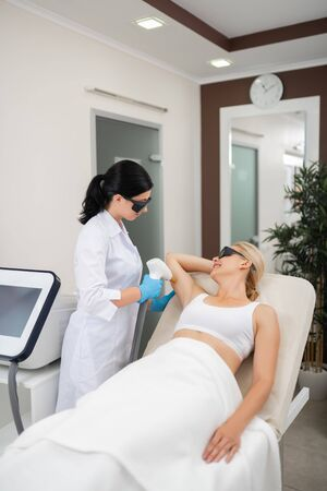 Excited to be beautiful. Pretty woman lying in a beauty salon smiling during laser procedures for her armpits.