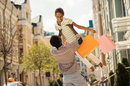 Loving parent. Amazing international girl keeping smile on her face while holding her bags after shopping Stock fotó