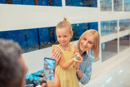 Photo of daughter. Daddy taking photo of daughter holding little hamster in hands while standing near mom