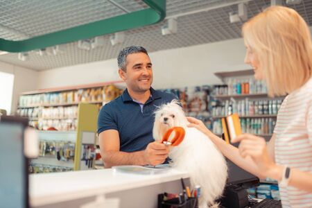 Talking to cashier. Grey-haired man smiling while buying orange dog lead and talking to cashier