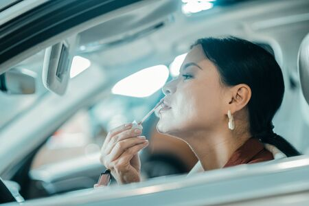Staying pretty. Beautiful woman putting on her lipstick sitting in the car getting ready for her working day.