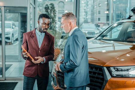 Showing options. Smiling car dealer with the tablet in his hands presenting different car models to a customer. Stock Photo