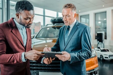 Insurance contract. Concentrated businessman signing a contract buying a car in a car showroom.