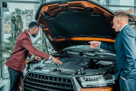 Exploring insides. Enthusiastic car showroom consultant showing his client things he pointing in the car under capote. Imagens