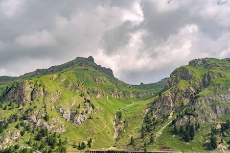 Beautiful nature with track on green high hiil under overcast with cloud sky Reklamní fotografie