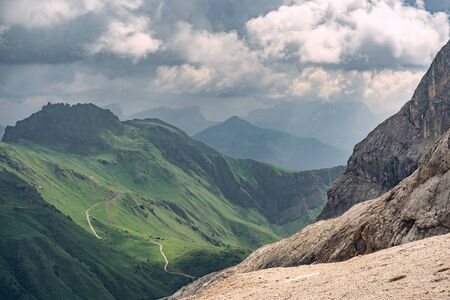 Beautiful Alps with rocky mountain and green hill under cloud sky in national park