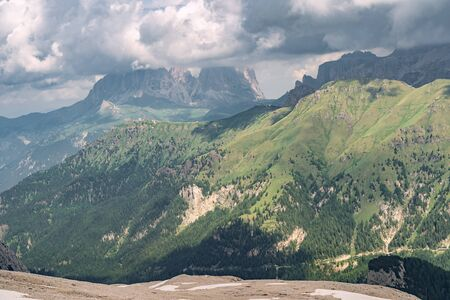 Scenic landscape with forest on green hill, rocky mountains and blue cloud sky in Alps