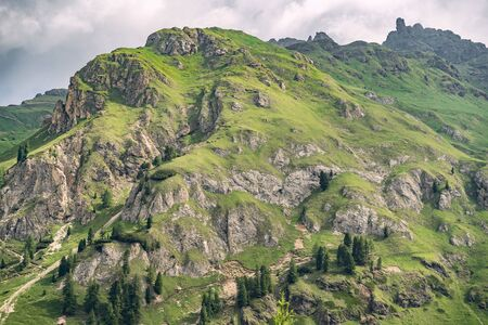 Scenery nature with high rocky and green hill under overcast sky in Alps