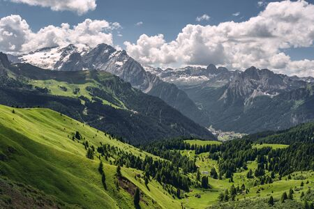 Beautiful nature with green hill near high rocky mountain and pine tree forest, under blue sky