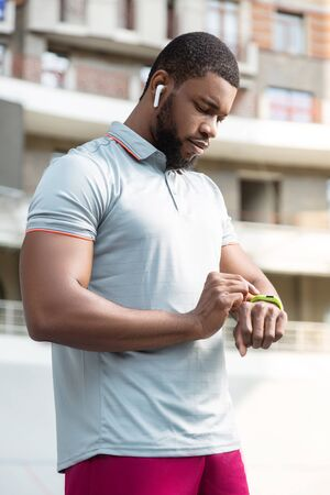 device. Healthy African American young man looking at his fitness tracker on the wrist during the workout outdoors