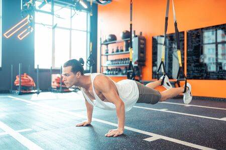 Physical activity. Handsome nice man doing pushups while working out in the gym