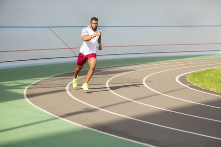 Young and fit. Bearded fit young African American professional male runner in stylish sportswear jogging at the stadium Imagens