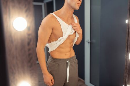 Perfect body. Handsome young man holding his t-shirt while looking at his body Stock Photo