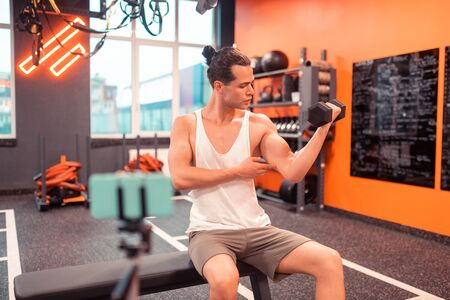 Strong muscles. Fit well built man showing his muscular arm while sitting in front of the camera