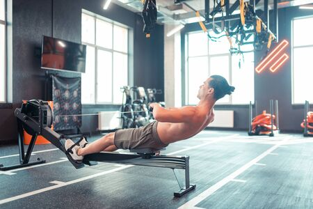 Exercise for training. Strong good looking man pulling weight on himself while doing the exercise for training