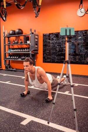 Additional weight. Serious hard working man doing pushups with dumbbells while training