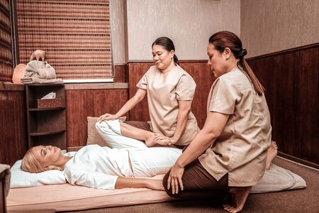 Staying beautiful. Two serious masseuses sitting near their client lying on a mat doing her leg massage. Banco de Imagens