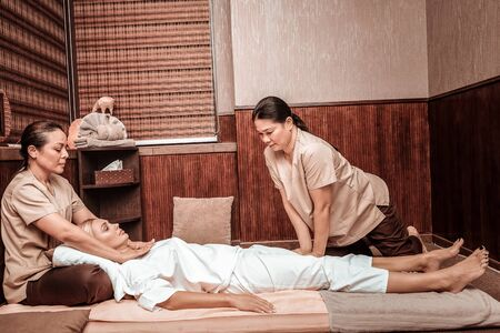 Thai massage salon. Two concentrated masseuses helping their calm client to relax massaging her neck and legs.