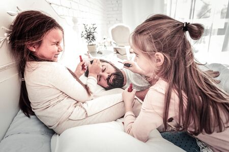 Cute sisters drawing on their dads face while he sleeps in the morning