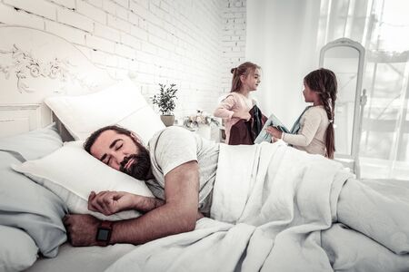 Sleeping dad with his two kids in background about to wake him up on a good day