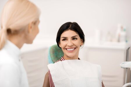 Glad to be healthy. Beautiful woman smiling sitting in front of her dentist being happy about her future teeth whitening.