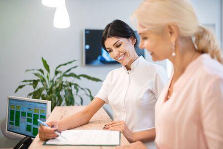 Apoyar a los pacientes. Mujer sonriente y su dentista alegre juntos llenando un formulario en el mostrador de recepción.