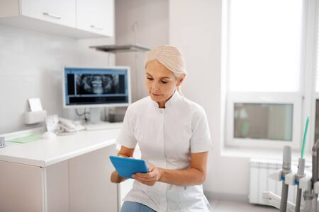 Double checking. Concentrated dentist looking at her tablet checking the date of her appointment with patient. Imagens