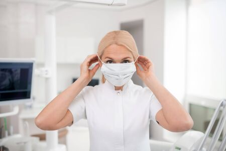 Ready to meet the patient. Dentist standing in her office putting on her surgical mask getting ready for appointment with the patient.