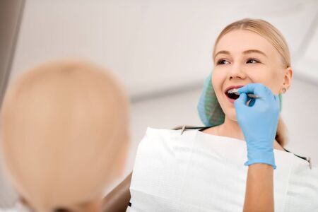 At dentists. Smiling young woman sitting in the chair in dental clinic having her braces examination.