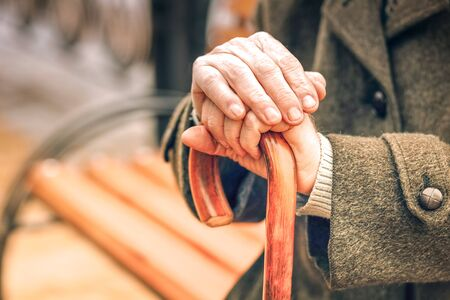 Close up of hands of elderly man leaning on cane on a fine day Stock Photo