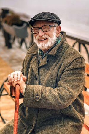 Retrato de un anciano sonriente sentado en un banco en el parque en un buen día Foto de archivo