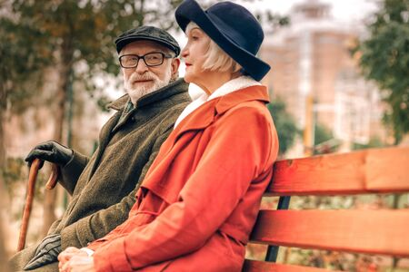 Senior man looking lovingly at his wife sitting on bench in park on a fine day Stockfoto