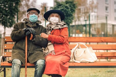 Ill senior couple with face masks relaxing on bench in park on a fine day