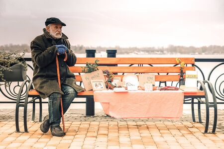 Miserable cold poor man sitting on bench in park on a fine day 写真素材